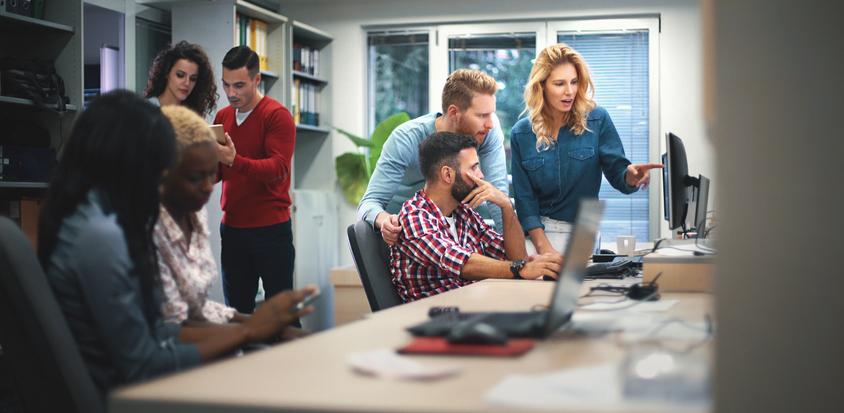 1人の女性と2人の男性がパソコン画面を見ながら話している